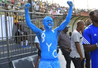 A Liberian football fan with body painted in blue cheers before a match between on 19 March 2017