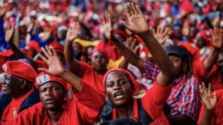 Mourners and supporters of the Movement for Democratic Change (MDC) party wave good bye to Zimbabwe's iconic opposition leader Morgan Tsvangirai who died last week after a battle with cancer, on February 20, 2018, during his burial at his rural village Humanikwa in Buhera.