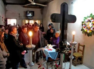 Varias personas están en un cuarto pequeño en medio de una ceremonia religiosa.