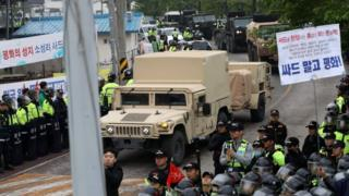 Protesters and police stand by as trailers carrying US THAAD missile defence equipment enter a deployment site in Seongju, early 26 April 2017.