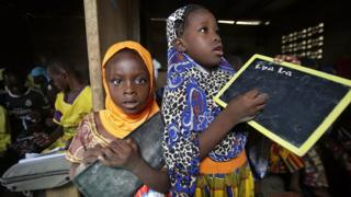 Girls pose with their chalkboards as they attend a class at a school in Abidjan, Ivory Coast, 17 November 2017