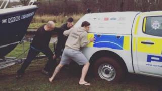 Man pushing stuck police boat