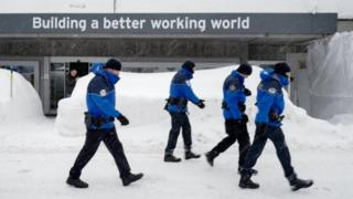 Policemen walk across show ahead of the opening of the World Economic Forum 2018 annual meeting