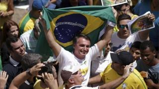 """Congressman Jair Bolsonaro holds a Brazilian flag during a protest against Brazil""""s President Dilma Rousseff, part of nationwide protests calling for her impeachment, in Brasilia, Brazil, March 13, 2016"""