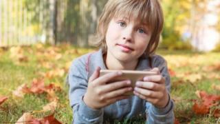 طفل يستخدم هاتف نقال