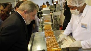 Lula observa trabalhador operando máquina que embala medicamentos