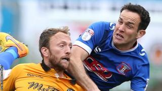 Carlisle's Luke Joyce climbs above Sean Rigg of Newport County