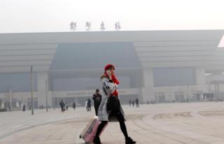 河南鄭州東火車站外一名旅客在霧霾下帶著口罩走過車站廣場(中新社圖片17/1/2017)