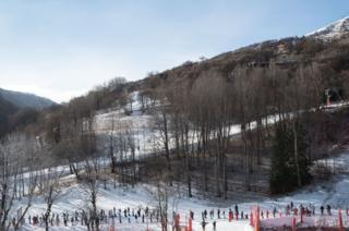 Skiers stand in line, waiting to have access to a mechanical ski lift