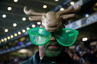 """Rugby Union - Championship - New Zealand All Blacks vs South Africa Springboks - Auckland, New Zealand - September 16, 2017 A fan of South Africa""""s Springboks wears a headdress and novelty glasses."""