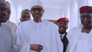Nigeria President Muhammadu Buhari dey waka with aides