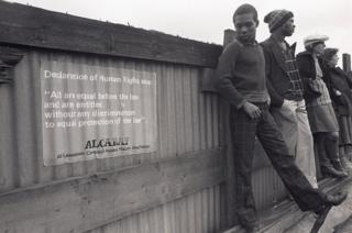 A young man stands next to an ALCARAF sign
