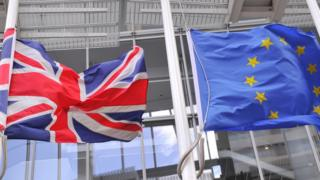 The British Union flag and the EU flag fly from flag poles in London