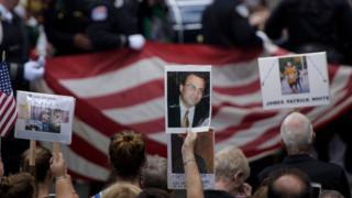 ニューヨークで開かれた9/11追悼式で犠牲者の写真を掲げる人々