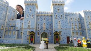 Лего-фигурки британского принца Гарри и Меган Маркл красуются у входа в также сделанный из Лего Виндзорский замок, а вместе с ними и конструктор этой модели Пола Лофтон.