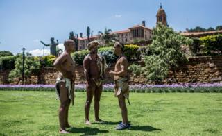 """Khoisan Chief SA (C), Khoisan community members Christian Martin (L) and Brendon Willings (R) talk as they camp during the 12th day, outside the South African government """"Union Buildings"""", in Pretoria on December 12, 2017. They were previously refused to enter the buildings by officials who complained about their traditional dress."""