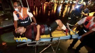 An injured man is helped by emergency rescue workers after an explosion on a passenger train in Taipei, Taiwan, Thursday, July 7, 2016