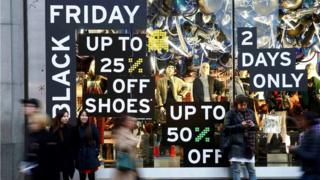 """Shoppers walk past a store promoting """"Black Friday"""" in London"""