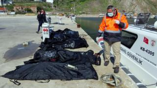 A rescuer walks next to bodies of refugees and migrants in body bags laid on a pier next to a Turkish coast guard vessel, after an inflatable boat carrying refugees and migrants sank off the Greek island of Lesbos and at least 16 people drowned, at the Aegean port village of Babakale in Canakkale province, Turkey, 24 April 2017