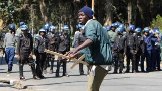 A protester holding a wooden cross in front of police in Harare, Zimbabwe - Wednesday 3 August 2016
