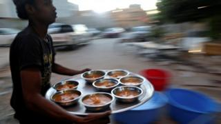 A man carries food to tables of Muslims eating their Iftar (breaking of fast) meal during Ramadan in Benghazi