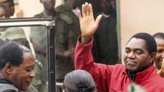 "Zambian opposition leader Hakainde Hichilema waves to supporters from a police van as he leaves a courtroom in Lusaka on April 18, 2017. Hichilema""s arrest on treason charges - after his convoy allegedly refused to give way to the president""s motorcade on a main road in the west of the country - has fanned political tensions in Zambia"