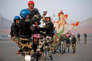 Women motorcycle riders perform in a daredevil display, India.