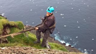 Espern climbs holding a gannet chick