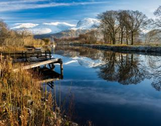 The serene Caledonian Canal is pictured by Angus Chisholm with a snow covered Ben Nevis in the background