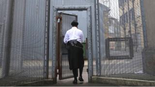 A prison guard opens a gate