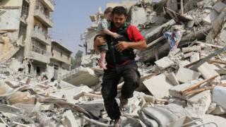 Hombre cargando un niño en Alepo