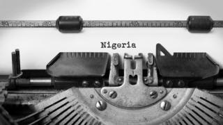 A typewriter with the word Nigeria typed on a piece of paper