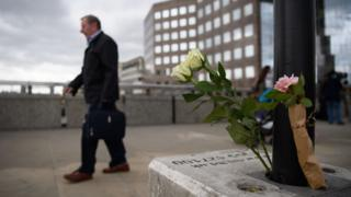 Man walks past floral tribute on London Bridge following the June 2017 attack