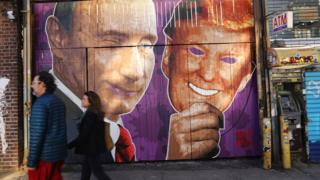 A mural depicting a winking Vladimir Putin taking off his Donald Trump mask is painted on a storefront in Brooklyn, New York.
