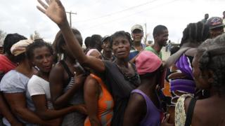 People queue for food and clothes being distributed at a shelter in Port-Salut, southwest of Port-au-Prince, on 9 October