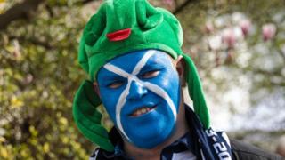 Шотландский футбольный фанат раскрасил лицо в цвета флага Шотландии. Так шотландцы готовились к игре со сборной Англии