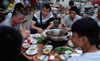 This photo taken on May 9, 2016 shows people eating dog meat at a restaurant in Yulin, in China's southern Guangxi region.