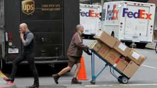 United Parcel Service (UPS) driver Grant Jung (R) pushes a handtruck loaded with boxes as he makes deliveries in San Francisco