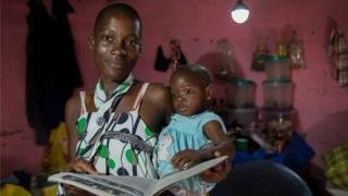 Woman reading to her baby under solar powered light