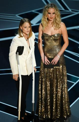 Jodie Foster with crutches and Jennifer Lawrence