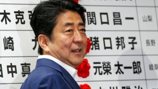 Japan's Prime Minister Shinzo Abe smiles as he puts a rosette on the name of a candidate who is expected to win the upper house election at the LDP headquarters in Tokyo, Japan on 10 July