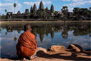 A young monk sits in front of a lack in front of the Angkor Wat temple on 1 January 2016, near Siem Riep, Cambodia.
