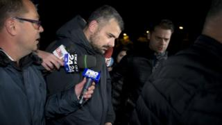 Costin Mincu (centre), one of the owners of the Colectiv nightclub, leaves the general prosecutor's office handcuffed in Bucharest, Romania 2 November 2015