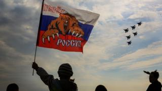 "A Russian boy waves flag with slogan ""Russia forward"" as ""The Russian Knights"" an aerobatic demonstration team of the Russian Air Force perform during the Moscow International Aviation and Space Salon"