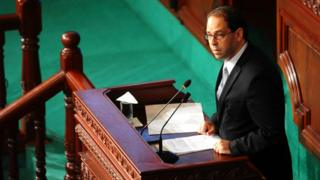 Newly named Tunisian Prime Minister Youssef Chahed, centre, delivers his speech at f the Parliament in Tunis, Friday 26 August, 2016 ahead of a confidence vote.
