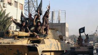fighters from the Islamic State group ride tanks during a parade in Raqqa, Syria on 30 June, 2014