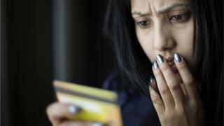 Женщина в ужасе смотрит на свою кредитку