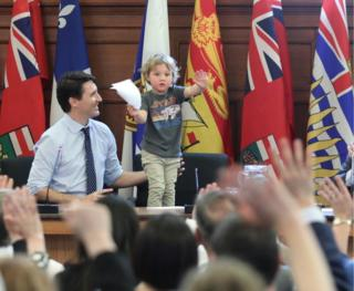 Trudeau junior stands on his chair in a press conference briefing room, holding up his hands to calm the press, who can be seen in soft focus with hands raised in the foreground.