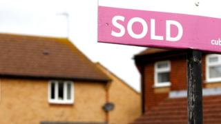 A sold sign outside of an out of focus house