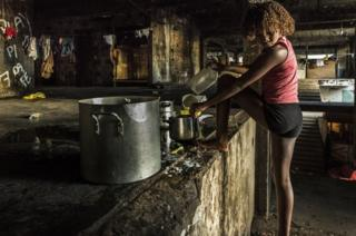 Girl washing the dishes in the main stairway of the occupied IBGE building, 'Favela' Mangueira community, Rio de Janeiro, Brazil.